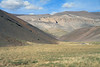 Down the tussock grass slope to the slopes along the Quebrada Paipote - with the cumulus clouds above - northern Copiapó province - Atacama region.