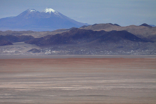 Across the southwestern Salar Atacama (salt flat) and the cloud-shadows upon the slopes and ridges of the Cordón Lila (mountain) - to Volcán Miñiques, peaking at around 19,390 ft (5,910 m) - Loa province - eastern Antofagasta region - this is the widest area of Chile, still only about 220 mi. (350 km) in width, along the 2,700 mi. (4,300 km) length of the country - this is also the widest section of the lengthy (10° N to 57° S), Cordillera Andes, extending for about 4,500 mi. (7,200 km) along western South America, here along its widest area (measuring about 450 mi./725 km).