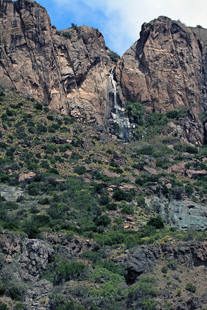 Cascada (waterfall) descending the igneous rock slope and ridge amongst the vegetation in the Waterfalls descending the igneous rock slope and ridge amongst the vegetation in the Patagonia Steep ecoregion - General Carrera province - Aisén region.
