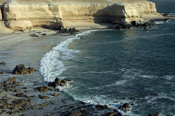 Volcanic rock and sedimentary sandstone shoreline along Bahia Moreno - amongst the Pacific wave breaking along the beach, during early-flood tide - Antofagasta region - northern Chile.