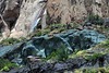 Mineral pigments fused into the igneous rock slope and fallen boulders, amongst the waterfall and Patagonia Steepe ecoregion vegetation - General Carrera province - Aisén region.