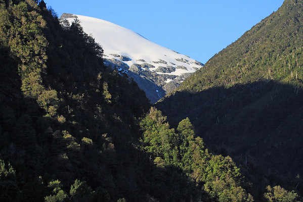 Sunlight and shadows upon the forested slopes and snow bank along the valley and pass between the Río Cisnes and Río Quelat - northeastern Aisén province - Aisén region.