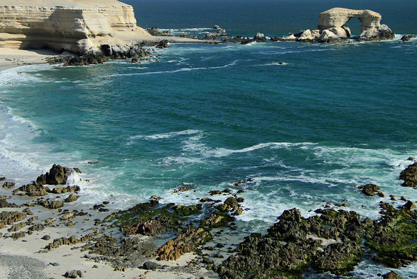 From the volcanic rock and marine algae along Bahia Moreno - beyond to the water-sculpted sea stack arch of The Gateway (La Portada) - a natural monument composed of igneous andesite (an extrusive or volcanic rock), while its cap is sedimentary sandstone - Antofagasta region - northern Chile.