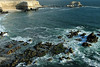 """Early-flood tide amongst the marine algae (sea weed) cloaked upon the volcanic rock shoreline, along Bahia Moreno - beyond to La Portada Natural Monument (1990) - """"The Gateway"""" a natural sea arch - Antofagasta region - northern Chile."""