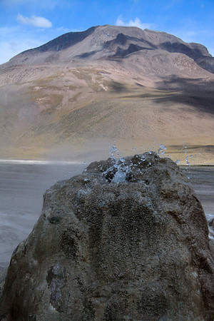 Geothermal vent amongst the airborne waterdrops and steam - Tatio Geyser Field - with above the cloud-shadows upon the slope along the Central Volcanic Zone of the Andes Mountains -  Loa province - northeastern Antofagasta region.