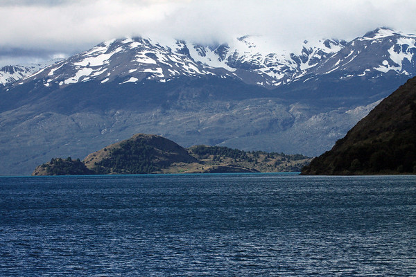 From the cloud-shadowed slope along the southern area of Lago General Carrera - beyond to the southern shoreline upon the island located just northeast from the discharge of Lake Carrera, into Lake Bertrand - and above the eroded slopes, ridges, snow banks, and clouds overlooking the mouth of the Rio Leones Valley - Aisén region.