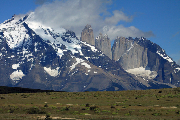 Across the patagonia steepe vegetation of cushion plants, xeric shrubs, and tussock grasses - up to Mt. Almirante Nieto, with its upper peak mostly concealed - to the distal Torres del Paine, with Central peaking at around 9,186 ft. (2,800 m), and Norte at about 7,375 ft. (2,248 m) - adjacent Cerro Nido Condo, displaying its igneous granite base and metamorphic hornfels cap rock amonst the early summer season snow banks - Última Esperanza province - Magallanes region.