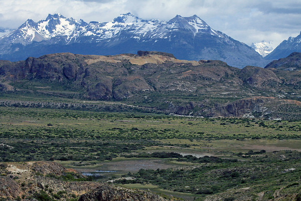 Estero del Bano and the vegetated valley - to the rock slopes and ridge overlooking the northern Laguna Verde - then beyond to the Sierra Avallanos, displaying its jagged ridges and peaks - with distal to the sunlit slope and ridge along the Ventisquero Valley near the Torres del Avellano - just south of 46° S latitude, near the active spreading center of the Antarctic-Nazca plate boundary, where it is being subducted beneath the South America continental margin, thus the Southern Volcanic Zone along the Cordillera Andes - General Carrera province, Aisén region.