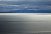 Sunlight upon the calm waters of the Bahia Inutil - to the shaded shoreline of Isla Dawson (l), and the distal slopes on the Bruswick Peninsula - Magallanes region, which is the southernmost, largest by land area, and 2nd to the least populous of all 16 regions in Chile.