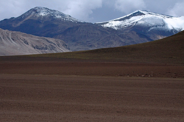 Across the iron oxide rich slope from Cerro Pabellón, a volcanic cone - to the southern edge Cerro Torta - then above the Volcán Tocorpuri complex, with its snow-cloaked crater rim (r) peaking at around 19,055 ft (5,808 m) - Loa province - northeastern Antofagasta region.