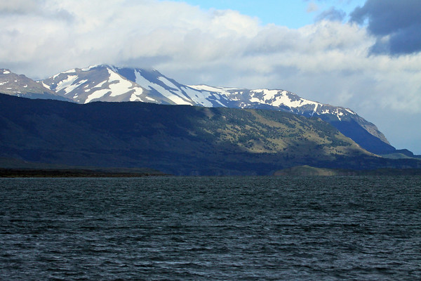 Mid-morning sunlight patch upon the snow banks along the Antonio Vargas Peninsula - with below the Islote Rata (l) and Isla Guanaco Island (r) amongst a sunlight patch - at the Seno Última Esperanza (sound) - Magallanes region.