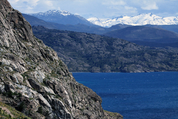 Steep rock slopes along the edge of the General Carrera National Reserve - below to the whitecaps upon Lago General Carrera - distal the snow-capped glaciers along the slopes and ridges above the southern area of Lago Plomo - in the Laguna San Rafael National Park - Aisén region.
