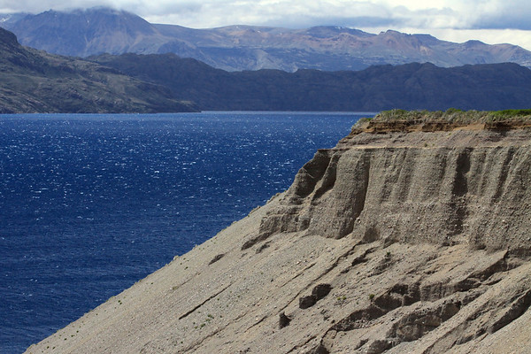 Sedimentary conglomerate rock slope eroded along the mouth of the Rio Horquestas - with below the whitecaps upon Lago General Carrera - then beyond the sunlight and cloud-shadows upon the slopes and ridges along the Levican Peninsula - with further (l) the slope below Cerro Piramide - Aisén region.