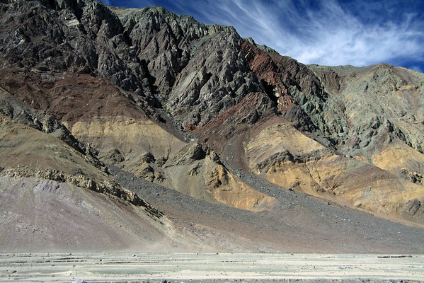 Colorful array of mineral pigments along the sedimentary rock slope and western headland, leading down to the mouth of the Quebrada Cortadera - from here along the river bed in the Quebrada Paipote - northeastern Copiapó province - Atacama region.