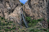 Waterfalls descending the igneous rock slope and ridge amongst the xeric shrubs, tussock grasses, cushion plants, and lithophytic lichens - General Carrera province - Aisén region.