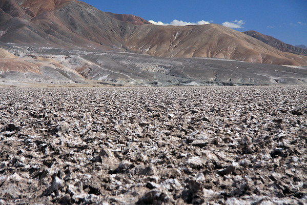 Across the caliche, a surface deposit consisting of sand or clay impregnated with crystalline salts - here upon the largest salt flat in Chile, the Salar Atacama - beyond to the mountain slopes and ridges along the Cordón Lila, along the southern area of the salt flat - Loa province - eastern Antofagasta region.