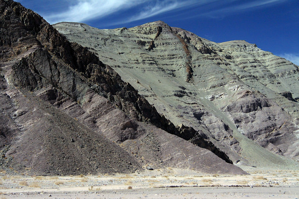 Igneous rock dykes (dikes) prutruding from the fractures amongst the sedimentary rock strata and scree fans - from here along the river bed of the Quebrada Paipote - northeastern Copiapó province - Atacama region.