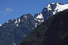 Early-summer season snow patches along the jagged igneous rock ridge, at the head of Aisén Fjord - from here amongst the sunlight and cloud-shadow upon the forested slope, northward from Puerto Chacabuco - here in the Valdivian Temperate Rainforest ecoregion - eastern Aisén province - Aisén region.