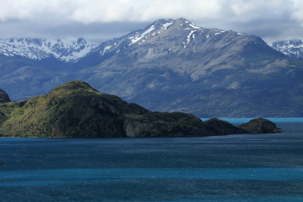 Isla Macías - the sunlight and shadows along its southern shoreline and  slopes - beyond across Lago General Carrera - to the snow-banks upon the slopes and ridges of the Sierra Avallanos, viewing (l) up the Rio Malas Valley - Aisén region.