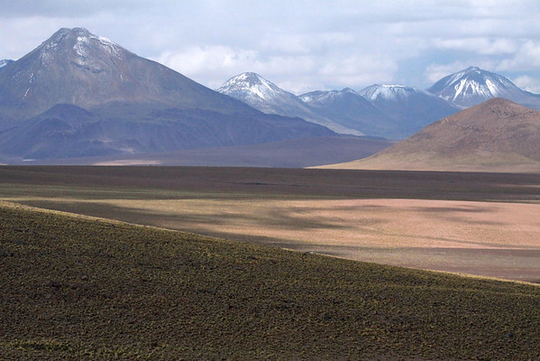 Across the mostly shadowed slope below Volcán Tatio - across to the sunlit Volcán Pabellón (r) - and Volcán Colorado (l) with distal (r) to Volcán Sairecábur, peaking at around 19,590 ft (5,971 m) - Central Volcanic Zone of the Cordillera Andes - Loa province - northeastern Antofagasta region.