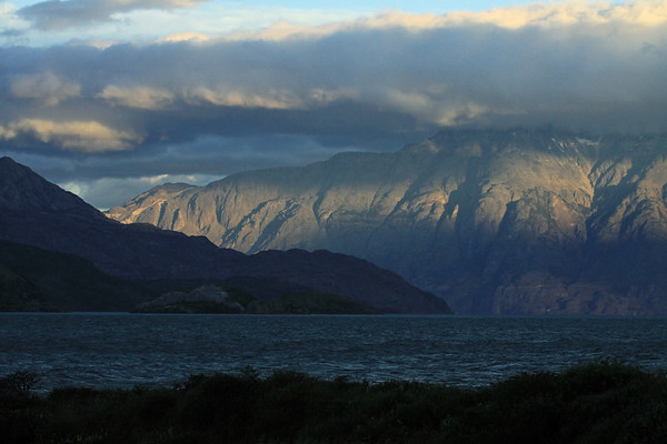 Day's last rays upon the southern slopes above Lago General Carrera, amongst the snow patches and clouds in the General Carrera National Reserve (1994) - with the Islas Malvinas in the shadowed foreground, adjacent the slopes of the Sierra Avallanos - from here along the shoreline of Puerto Tranquilo - Aisén region.