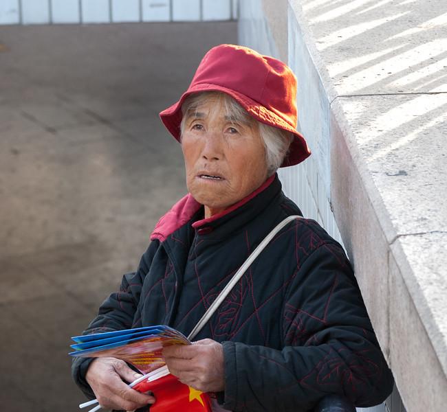 A woman sells maps and flags near Tiananmen (Xicheng, Beijing, CN - 10/23/13, 4:17:26 PM)