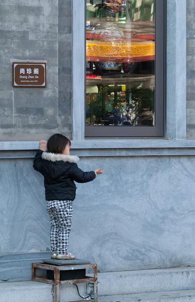 A child plays outside an antique shop on Qianmen Dajie (Xicheng, Beijing, CN - 10/23/13, 3:28:56 PM)