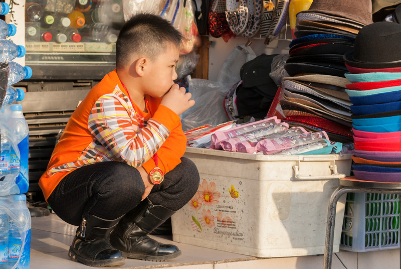 A child surveys the stream of tourists at a stall near Tiananmen (Xicheng, Beijing, CN - 10/23/13, 4:19:38 PM)