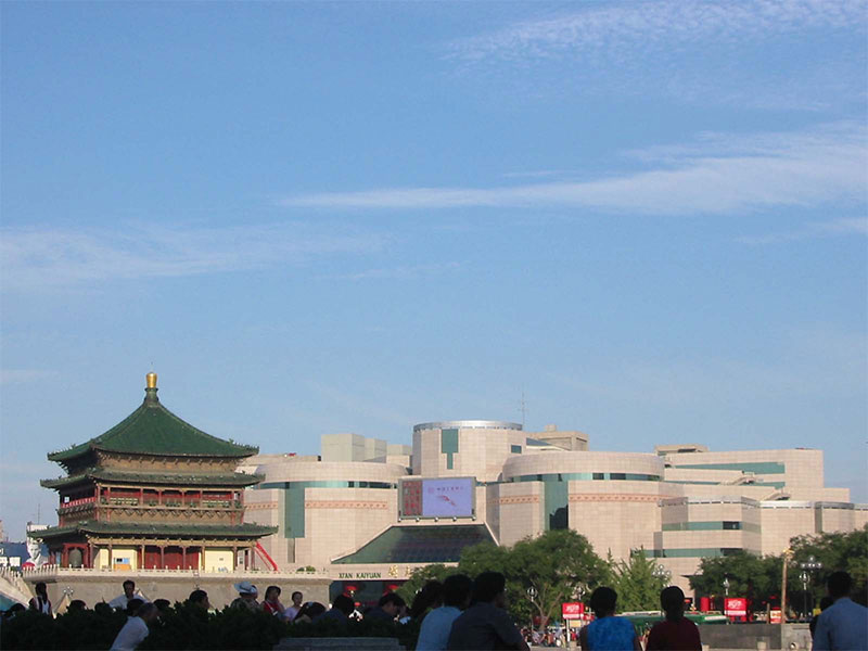 """Xi'an's Ming Dynasty Bell Tower juxtaposed with a striking modern building, as seen from across the street at """"Bell Tower Square'."""