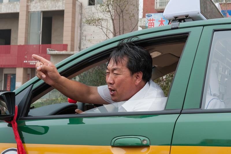 A Yuanqu cab driver points the way to town. (Yuanqu, Yuncheng, Shanxi, CN - 07/21/12, 12:41:37 PM)