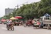 A motorcyclist rides past streetside produce vendors. (Yuanqu, Yuncheng, Shanxi, CN - 07/21/12, 1:39:26 PM)