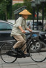 A man wearing an old-school hat bicycles in central Beijing. (Dongcheng, Beijing, CN - 08/13/06, 2:02:45 PM)