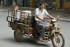 A man and boy ride a motor-wagon on a Yanshi street. (Yanshi Shi, Luoyang Shi, Henan Sheng, CN - 08/16/06, 12:51:39 PM)