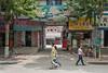 Pedestrians walk past shops and the entrance to a courtyard on a Yanshi street. (Yanshi Shi, Luoyang Shi, Henan Sheng, CN - 08/16/06, 12:59:31 PM)