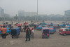 Various types of taxicabs are parked on the plaza of the Yanshi Train Station awaiting passengers to arrive. (Yanshi Shi, Luoyang Shi, Henan Sheng, CN - 08/16/06, 8:54:31 AM)
