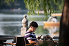 A man checks his messages in the late afternoon sun at a cafe on Beijing's Houhai Lake (07/26/11, 4:58:03 PM)