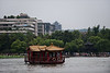 A sightseeing boat sets out from the shore of Xi Hu (West Lake) in Hangzhou, Zhejiang, as summer tourists congregate at a nearby lakeshore pavilion. Enormous Chenghuang Pavilion is visible on a distant  hilltop. (07/23/11, 4:56:04 PM)