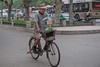 A man bicycles through Luoyang with a basket of birds. (Luoyang, Henan, CN - 07/10/11, 5:45:10 PM)