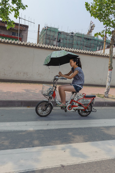 A girl manages to steer her scooter with one hand while using her other hand to keep her parasol positioned properly. (Chanhe, Luoyang, Henan, CN - 07/11/11, 10:45:11 AM)