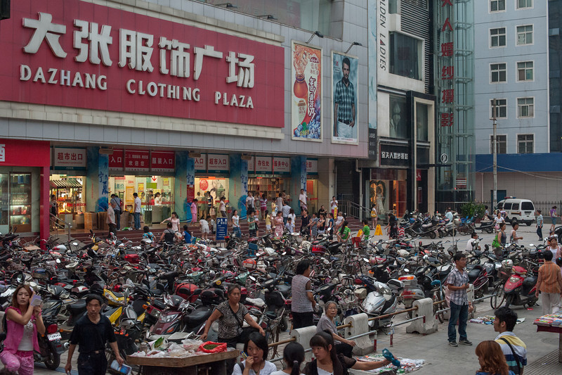 The plaza in front of a Luoyang clothing store is used as a makeshift parking lot for scooters and bicycles. (Luoyang, Henan, CN - 07/10/11, 7:34:31 PM)