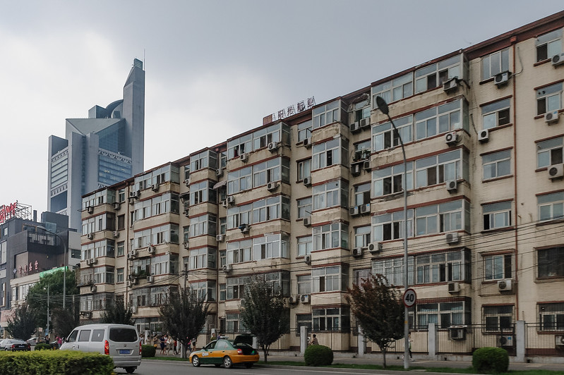 An older, standard-issue Beijing apartment block is seen juxtaposed with a new, ultra-modern syscraper (Chaoyang Qu, Beijing Shi, CN - 07/10/12, 6:12:00 PM)