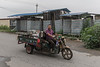 A man drives on a road in Anyang's Xiaotun Village past storage crates filled with archaeological artifacts near the entrance to the Yinxu Archaeological Field Station. (Anyang Shi, Henan Sheng, CN - 07/15/16, 12:34:33 PM)