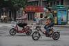 Two women navigate an Anyang intersection on mopeds. (Anyang Shi, Henan Sheng, CN - 07/15/16, 1:16:47 PM)