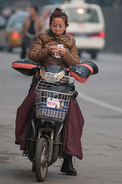 A woman checks her phone while waiting at a Wangfujing Street stoplight. (Chaoyang, Beijing, CN - 10/22/13, 11:07:49 AM)