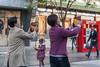 Two women record video on their iPads as they walk along the Qianmen Street shopping area. (Xicheng, Beijing, CN - 10/23/13, 3:33:36 PM)