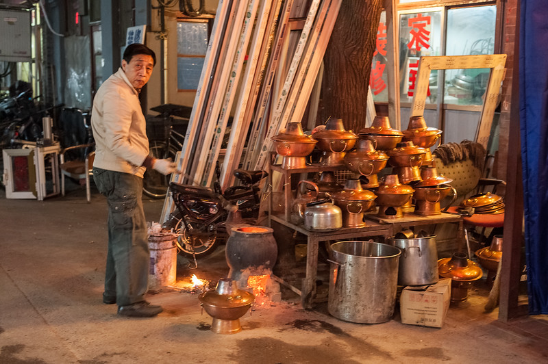 A man prepares traditional Beijing hotpot in front of his hutong restaurant. (Dongcheng, Beijing, CN - 11/11/13, 9:30:46 PM)