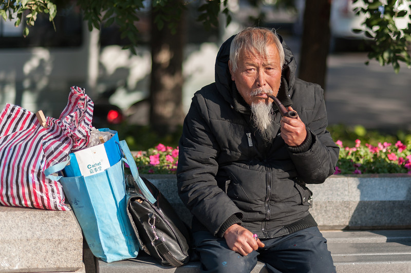 An old-timer enjoys his pipe in a central Beijing plaza. (Dongcheng, Beijing, CN - 10/24/13, 9:24:29 AM)