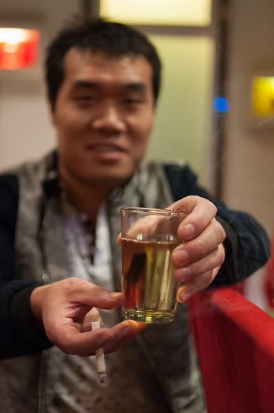 A man proffers a glass of Beijing-brewed Snow beer. (Dongcheng, Beijing, CN - 10/22/13, 10:27:22 PM)