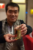 A man proffers a glass of Beijing-brewed Snow beer. (Dongcheng, Beijing, CN - 10/22/13, 10:27:22 PM)