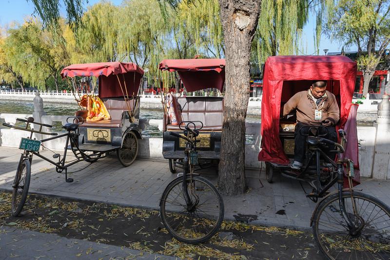A Shichahai hutong pedicab tour guide takes a break by Houhai lake. (Shichahai, Xicheng, - 11/14/13, 1:12:55 PM)